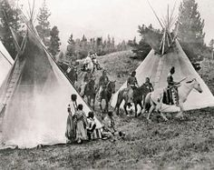 A group of Blackfeet men and women riding in to camp; all in native dress. The men lead, the women are behind pulling travois. Glacier Park, Montana environs. circa 1910.