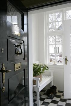 Black and white entry hall. Love the glossy black door. Double entry lets you deposit boots etc and have an airlock during the Winter months.