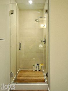 Shower w/ teak (?) flooring, glass door - small but nearly spa like