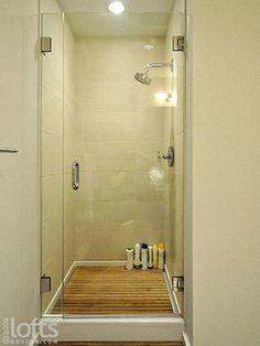Shower w/ teak (?) flooring, glass door - small but nearly spa like