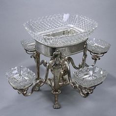 OLD SHEFFIELD SILVER PLATED EPERGNE CENTERPIECE : Circa 1830, an elegant antique silver plated centerpiece supported by four floral paw feet, complete with matching suite of contemporary cut crystal bowls; plain oval shape with four-branched detachable arms. L: 18 1/2 in.(47cm) x H: 8 7/8 in.(22.5cm)