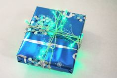 For the next-level giver: Use mini LED lights to wrap a little gift! Simply add batteries to the light pack, then use it as ribbon, keeping the battery pack on the bottom. Turn on when ready to give — guaranteed to be the most eye-catching gift in the room!