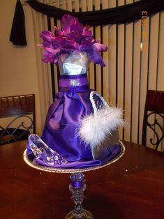 Centerpiece for a Quinceanera (Sweet Sixteen).. made with paper mache using a wire dress form (Michaels) as a base. Decorated it with silk flowers, fabric, crystal shoe and purse. For paper mache, just mix one cup water to one cup flour and newspaper or paper bag strips.  Once the shape is done and dry (1 day)  cut slit on back and take out shell. Base from dollar store: (2 candle sticks and silver tray). Paint bust with silver paint (Can)