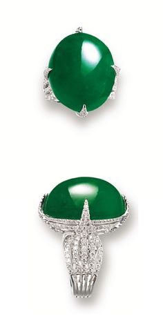 JADEITE AND DIAMOND RING. The highly translucent oval jadeite cabochon of intense emerald green colour, to stylised mount set with brilliant-cut diamonds together weighing approximately 3.00 carats, mounted in 18 karat white gold. Ring size: 6½ Cabochon approximately 23.62 x 19.72 x 12.60mm.
