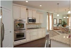 white kitchen with double ovens and built-in microwave