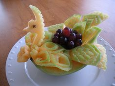 Melon Bird Basket    .Cantaloupe carving into a bird like basket garnish with grapes.