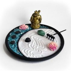 Miniature desktop zen garden featuring a mini Laughing Buddha statue! The glass zen garden base has a crescent moon design to separate the crushed glass from the sand. Use the rake to create designs in the sand and arrange the miniatures any way you like! Use as many or as little as you prefer. Stack the stones or line them up to make a path! Great for display on any desk, bookshelf, or table top. Perfect gift for coworkers, loved ones, or yourself! Tumbled Gemstone will be selected at…