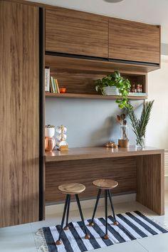 Decoração com influencias brasileiras com madeira e ambientes integrados. Nos detalhes da decoração bancada de madeira, com bancos de madeira e adornos.