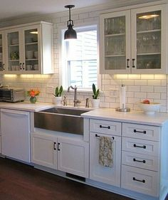Love the dark wood floors with the two colors of cabinetry, glass upper cabinets, and white and black appliances and countertops....