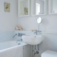 "7 Ideas for a Tiny Bathroom: • Three mirrors hung high create a ""window,"" with a functional makeup mirror below. • Ledges along the mirrors and wall create storage space for bath products. • Iridescent tile subtly reflects light without overwhelming the small space. • Light gray and blue offset the white of the porcelain fixtures and mirrors."
