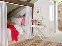 A simple tension rod and curtains create a private sleeping nook. In neutral shades with pops of red, stripes and floral patterns to play nicely together in this country bedroom.