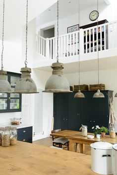 Beautiful hanging vintage pendant lights make the most of this incredible high ceiling in this new arts and crafts kitchen by deVOL