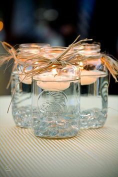 Mason jar centerpieces with floating candles. [UPDATED These DIY Mason Jar Centerpieces can also be made into favors. Use the lanterns to provide light to your wedding tables. Floating Candle Centerpieces, Rustic Wedding Centerpieces, Diy Centerpieces, Quinceanera Centerpieces, Easy Table Decorations, Wedding Tables, Wedding Ceremony, Wedding Cake, Rustic Candles