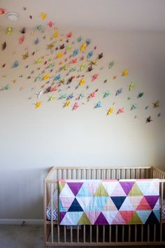 Folded paper cranes add texture and beauty to the walls (and ceiling) in Elise's Origami Crane Nursery. #estella #kids #decor