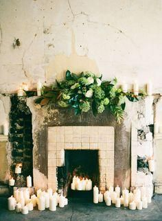 Love this voluminous garland of magnolia greenery and hydrangeas on this antiqued mantle and fireplace dotted with pillar candles.