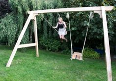 Wooden oak swing frame with children's swing (being used by an adult) and a baby swing