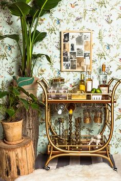 A little old school, a little retro - brass bar cart, candlesticks, gold etched glasses, bird wallpaper