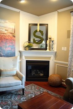 Corner fireplace - great idea using mirror and letter - molding over top is great too