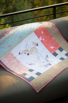 """A finished baby girl quilt featuring an adorable baby deer panel from Hawthorne Threads' fabric collection, """"Fawn""""."""