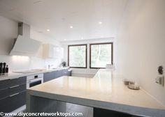 Valkoinen betonitaso sopii erittäin hienosti mustaan keittiöön. Hieno kontrasti.