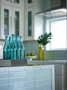 The island front, clad in frosted-glass subway tile is topped with marble.