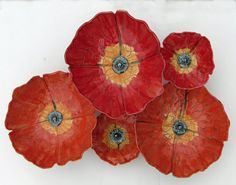 Poppies by Amy Meya. Hand sculpted porcelain poppies are an eye catching burst of color for the wall. Inspired by a recent trip to the Caribbean where colors abound, from the flowers, to the houses and the rainbows in the sky everyday. Each piece is carved free-hand, making them truly a one of a kind piece of art. The dimensions on the large poppies are approximately 12'' in diameter, and the height of the stems varies from 1'' - 5'', this allows more depth for a grouping of three or more…