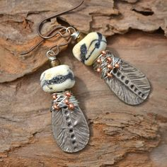 """*White Copper Embelished Feathers connected to beautiful Black and White Etched Lampwork Beads. Lots of rough wire wrapping with tiny bronze seed beads swirling around the base metal wire. These Earrings hang approximately 2"""" from the top of the Hypoallergenic Niobium earwire."""
