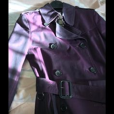 Burberry plum/Burgundy size 2 cotton trench NWOT NWOT, with a sheen, so it changes tones in different lighting. Not metallic, in storage since purchase at south coast plaza, Costa Mesa, CA nice and light for spring/summer dressy nights! Burberry Jackets & Coats Trench Coats
