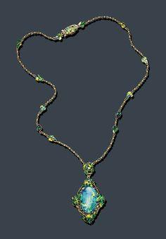 Louis Comfort Tiffany,  The pendant, set with an oval black opal within a multicolored enamel and gold grapevine frame, enhanced by oval-cut demantoids and old mine-cut sapphires, is suspended from a small cluster of similar design, set with an old mine- cut demantoid, attached to a gold and multicolored enamel grapevine link chain, mounted in gold, circa 1920--18 ins. long.