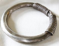 Solid silver bracelets made by the Hmong in this expandable style were popular with the Wa and Lawa, a minority hill tribe group of Southeast Asia. It is made from solid cast high grade silver (over 90%) with a bound split coil the contours of which have been smoothed over from wear.