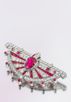 An Art Deco platinum, ruby and diamond brooch. In an intricate openwork fan form, containing one pear shape ruby, 42 calibre cut rubies, 14 round and square mixed cut rubies, one trapezoid cut diamond, one shield cut and two double chisel point cut diamonds, two baguette cut diamonds, and 80 transitional brilliant cut diamonds. #ArtDeco
