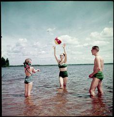 Man, woman and young girl playing with a beach ball in the water at the beach / Un homme, une femme et une fillette à la plage jouent dans l'eau avec un ballon