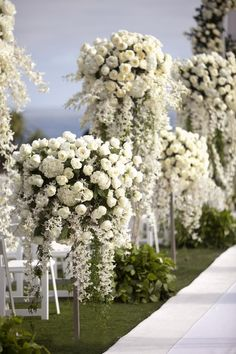 The white aisle runner was lined with heavenly floral arrangements in varying heights. Photography: Aaron Delesie Photographer. Read More: http://www.insideweddings.com/weddings/all-white-beach-ceremony-sophisticated-ballroom-reception/364/