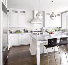 white cabinets, stainless steel, light counters, wood floor