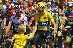 Team Sky rider Chris Froome of Britain (C), race leader's yellow jersey, shakes hands with a child before the start of the 188-km (116.8 miles) 11th stage of the 102nd Tour de France cycling race from Pau to Cauterets in the French Pyrenees mountains, France, July 15, 2015. REUTERS/Stefano Rellandini