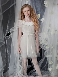 The Elora is a fairy-like dress with an ethereal quality, in taupe satin and tulle with an ivory cotton flower ruffle detail at the neck.. A matching grosgrain ribbon belt completes the effect. Simple and lovely.