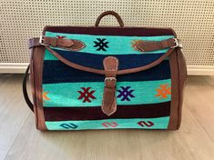 Exclusive travel bag made from Kilim rugs from Morocco.  35 x 55 cm/ 13.7 inch x 21.6 inch.  This bag is made of Berber Kilim rugs. Which are handwoven on a loom by Berber women from the middel Atlas Mountains of Morocco with sheep and camel wool and coloured with vegetable dye. Using century's old handcrafting technics. With leather straps.