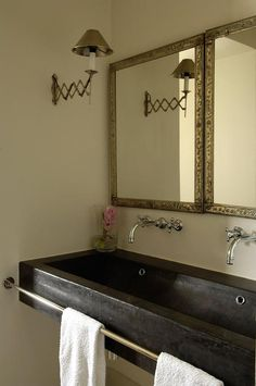 Chic bathroom features a black trough sink accented with a brass towel bar situated under his and her wall-mount faucets and hammered metal mirrors illuminated by accordion sconces