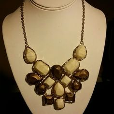 Bronze and cream colored stone necklace This is a beautiful statement piece necklace. Bronze and cream colored stones hang from a gold tone chain. The necklace is approximately 10 inches long with a 2 inch extension. Jewelry Necklaces