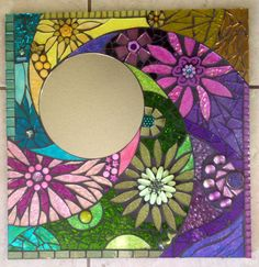 Titled Garden Rays, This is an all handcut, handmade mosaic mirror. I had alot of fun making this. It is one of my smaller peices at 16 X 16