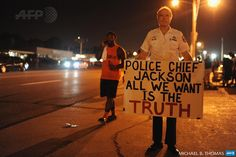 UNITED STATES, FERGUSON : Retired Captain Ray Lewis (R) of the Philadelphia Police department display a sign during a peaceful protest on West Florissant Avenue in Ferguson, Missouri on August 23, 2014, two weeks after the fatal shooting of Michael Brown. AFP PHOTO / Michael B. Thomas