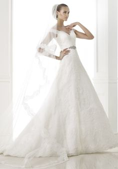 PRONOVIAS Off-The-Shoulder A-Line Wedding Dress in Rebrodé Lace and Tulle An off-the-shoulder wedding dress in A-Line silhouette with rebrodé lace appliqués cascading to the skirt, featuring a open V-back with scallops front and back. It has a chapel train.