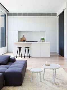 Kitchen Design Idea - White, Modern and Minimalist Cabinets | A few black details, including the stools, the stove, and the sliding barn door, interrupt the all white cabinetry in this modern kitchen.