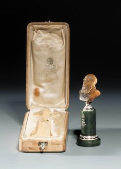 A smoky-quartz carved Bust of Tsar Alexander III on a gem-set enamel and nephrite Pedestal by Fabergé, workmaster Henrik Wigström, St. Petersburg, 1908-1917  The bust realistically carved, the tsar wearing the order of St. George, in the original velvet and silk lined wooden case, the cover stamped in Russian 'Fabergé St. Petersburg Moscow, London' with Imperial warrant 3¾in. (10cm.) high