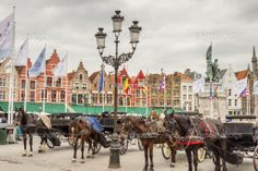Horse-drawn carriages in the main square in Bruges