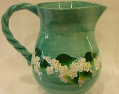 This heavy cobalt blue glass pitcher has been hand painted with a beautiful vine of white flowers, green leaves and lavender butterflies. The