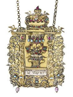 A POLISH PARCEL-GILT SILVER AND GEM-SET TORAH SHIELD rectangular form, applied with panels of foliage inhabited by monkeys, cranes and squirrels, centered by a gem-set basket of flowers flanked by spiraled columns, all surmounted by a crown, with four birds at the top, with one later portion plaque. ummarked except for Crakow control mark for 1806/07 height 8 5/8 in. 22 cm 18th Century