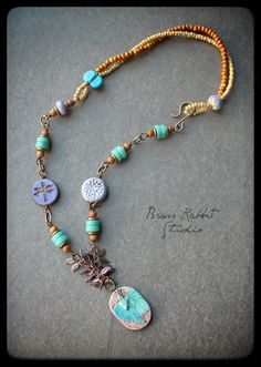 Mixed media, Bohemian style necklace with a beautiful ceramic pendant by Mary Harding, hung from a short section of copper fringe chain, handmade seaglass wirewrapped with sandalwood and brass disks, double strand of picasso finish, czeck glass seed beads with a lampwork round and wingding by Genea on either end, czeck glass table c