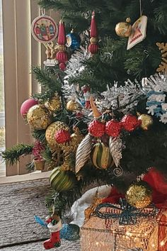 A Christmas tree with its decorations concentrated on just a few branches. With a whale, red bulbs, gold bulbs, green bulbs, silver bulbs, teddy bears, light up presents, and more