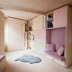 Studiomama has overhauled this tiny house in London with built-in furniture including a fold-out bed, and extendable dining benches with pink cushions.